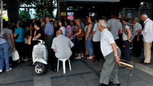 Pensioners queue outside a national bank branch, as banks opened only for pensioners to allow them to withdraw their pensions, with a limit of 120 euros, in Thessaloniki, on July 3, 2015. Greece is almost evenly split over a crucial weekend referendum that could decide its financial fate, with a 'Yes' result possibly ahead by a whisker, the latest survey Friday showed. Prime Minister Alexis Tsipras's government is asking Greece's voters to vote 'No' to a technically phrased question asking if they are willing to accept more tough austerity conditions from international creditors in exchange for bailout funds. AFP PHOTO /SAKIS MITROLIDIS        (Photo credit should read SAKIS MITROLIDIS/AFP/Getty Images)