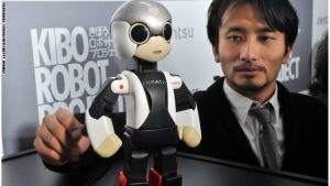 """This picture taken on December 19, 2013 shows Japanese robot creator and associate professor of the University of Tokyo, Tomotaka Takahashi (R), chatting to a small humanoid robot named """"Mirata"""", who is the twin brother robot to the world's first astronaut robot """"Kirobo"""" in Takahashi's laboratory at the University of Tokyo. Korobo, the world's first robot astronaut, has begun chatting on December 20, 2013 to the Japanese commander of the International Space Station, in what was being billed as the first conversation of its kind.   Kirobo, a pint-sized android equipped with artificial intelligence and capable of learning how to respond appropriately to humans, even put a marker down for Christmas, telling Koichi Wakata he expected a visit from a certain man bearing gifts.        AFP PHOTO / Yoshikazu TSUNO        (Photo credit should read YOSHIKAZU TSUNO/AFP/Getty Images)"""